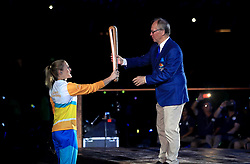 A torchbearer hands the baton to Chairman of Gold Coast 2018 Peter Beattie during the Opening Ceremony for the 2018 Commonwealth Games at the Carrara Stadium in the Gold Coast, Australia.