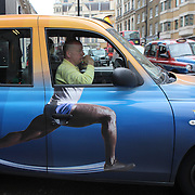 A humorous moment as a London Taxi driver prepares to pull into traffic in London city centre with a clever advertising logo on the side of the cab. London prepares for the 2012 Olympic games, UK. 16th July 2012. Photo Tim Clayton