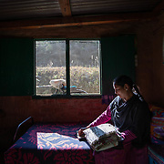 Mamta Pandey sits in her home 20km from Ranikhet, India on Dec. 6, 2018, going through her older work from years before she joined the women's knitting circle.