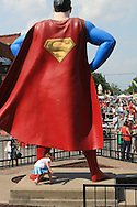 Little girl quietly sneaks under giant superman statue's cape while crowds fill the streets during three day Superman Celebration in mid June; Metropolis, Illinois.