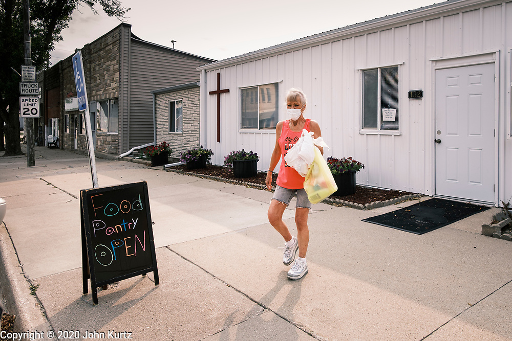 """16 SEPTEMBER 2020 - MITCHELLVILLE, IOWA: People leave the pantry at the Heritage Word of Life Church. There is no grocery store in Mitchellville, a small community in eastern Polk County. It doesn't qualify as a """"food desert"""" under USDA guidelines because there are grocery stores within 10 miles in neighboring communities, but based on state data, Mitchellville is the poorest community in Polk County (which includes the Des Moines metropolitan area). The Mitchellville zip code has the lowest per capita income in Polk County. Many people don't own cars and can't get to neighboring communities to buy groceries. Every day someone from the Mitchellville library picks up hot meals from a nearby town and distributes them in the library. Heritage Word of Life, a church across the street from Library, has a food pantry in their Fellowship Room where people can pick up fresh vegetables, staples, and hygiene needs.        PHOTO BY JACK KURTZ"""