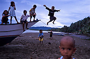"In the village of Busok Busok village poor children play with whatever comes to hand to have fun in the hours when they are not at school. Seen here playing and swinging on a ""banka"" a fishing and transport boat Aurora province, Philippines"