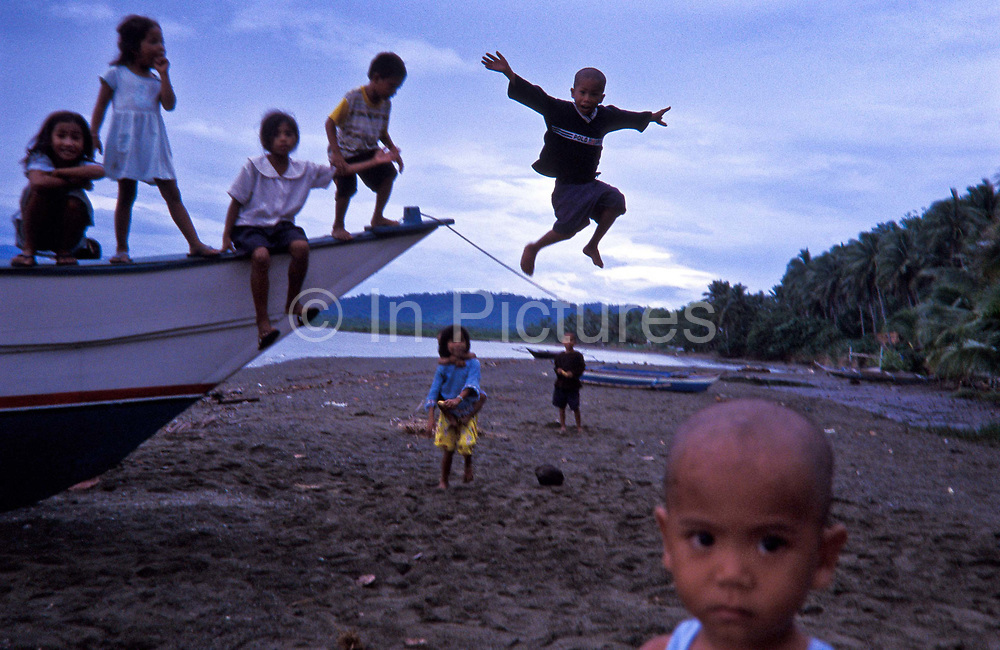 """In the village of Busok Busok village poor children play with whatever comes to hand to have fun in the hours when they are not at school. Seen here playing and swinging on a """"banka"""" a fishing and transport boat Aurora province, Philippines"""