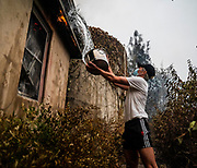 Brooks Corrigan of New York extinguishes a flame burning his fatherÕs neighborÕs property in Calistoga on Monday, Sept. 28, 2020.
