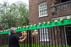 London, UK. 14 June, 2019. A man adjusts tributes to those who lost their lives in the Grenfell Tower fire beneath the tower on the second anniversary of the tragedy on 14th June 2017 which claimed the lives of 72 people and injured over 70 more.