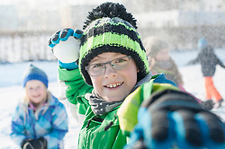 Portrait of boy throwing snowball