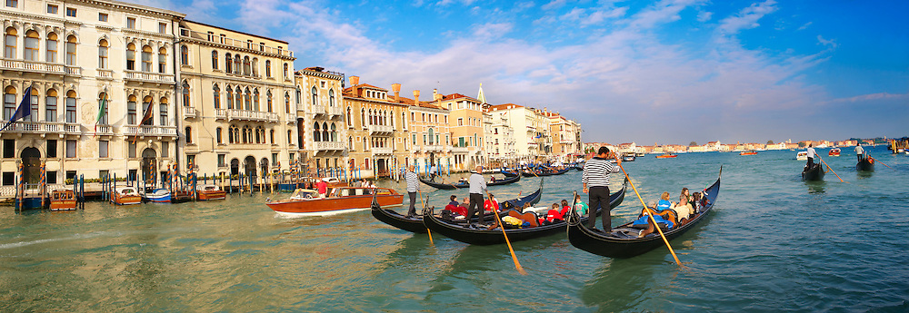 Gondolas on the Grand Canal - Venice - Italy .<br /> <br /> Visit our ITALY HISTORIC PLACES PHOTO COLLECTION for more   photos of Italy to download or buy as prints https://funkystock.photoshelter.com/gallery-collection/2b-Pictures-Images-of-Italy-Photos-of-Italian-Historic-Landmark-Sites/C0000qxA2zGFjd_k . The gondola ( góndoła ) is a traditional, flat-bottomed Venetian rowing boat, well suited to the conditions of the Venetian lagoon.  gondolas are typically propelled by a gondolier, who uses a rowing oar, which is not fastened to the hull, in a sculling manner and also acts as the rudder. The oar of the  gondola rests in an elaborately carved wooden rest (forcola) shaped to project from the side of the craft so as to allow the slight drag of each return stroke to pull the bow back to its forward course. For centuries, the gondola was a major means of transportation and the most common watercraft within Venice. .<br /> <br /> Visit our ITALY HISTORIC PLACES PHOTO COLLECTION for more   photos of Italy to download or buy as prints https://funkystock.photoshelter.com/gallery-collection/2b-Pictures-Images-of-Italy-Photos-of-Italian-Historic-Landmark-Sites/C0000qxA2zGFjd_k
