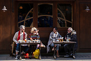 On the day that the UK government eased Covid restrictions to allow non-essential businesses such as shops, pubs, bars, gyms and hairdressers to re-open, customers enjoy outdoor snacks on Old Compton Street in Soho, on 12th April 2021, in London, England.