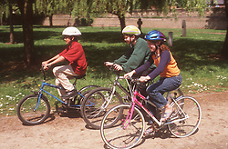 Group of children cycling through park wearing cycle helmets,