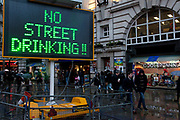 Controlled Drinking Zone sign lit up in central London warns people that drinking in public on the street is banned in this area.