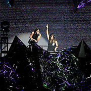 """Sisters Yasmine and Jahan Yousaf of the band Krewella perform in front of the """"Light Volcano"""", during the Verge Campus Spring Tour concert at the CFE Arena on the University of Central Florida campus, Tuesday, April 8, 2014, in Orlando, Florida.  (AP Photo/Alex Menendez)"""