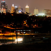 Downtown Kansas City MO skyline after nightfall with train motion blur in foreground.