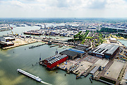 Nederland, Zuid-Holland, Rotterdam, 10-06-2015; Heijplaat met RDM campus, gezien vanaf de Nieuw Maas. Voormalige werf van de Rotterdamsche Droogdok Maatschappij (RDM) met de onderzeebootloods in de voorgrond (het rode gebouw), Waalhaven in de achtergrond.  <br /> Former shipyard of the Rotterdam Drydock Company (RDM), the submarine hangar in the foreground.<br /> luchtfoto (toeslag op standard tarieven);<br /> aerial photo (additional fee required);<br /> copyright foto/photo Siebe Swart