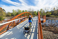 Woman rides her bike and pulls her child in a cart behind her on the Northwest Arkansas Greenway near Springdale Arkansas on a beautiful Autumn day<br /> <br /> Photography by Wesley Hitt