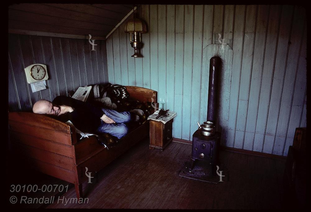 "Sigurjón Jóhannsson curls up on bed beneath clock-and-calendar beside coal stove in his farmhouse at Kot beneath Hekla; ""Old Man and Time""*; Rangárvellir, Iceland"