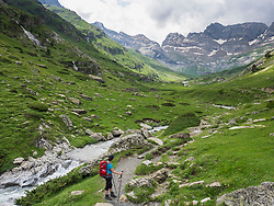 Woman hiking in the High Pyrenees with cirque d'Estaube in the background, Gavarnie, France
