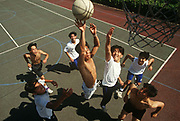 Teenage students jump high on a basketball court to score a goal at the Gyosei International Japanese School, a boarding school for Japanese ex-pats opened in 1987 in Willen Park, Milton Keynes, England. Seen from an aerial perspective, we look down on these active and fit young men, whose sense of competition and fitness is played out below us. Leaping up to help win the ball that is about to be placed in the foreground basket, each of the seven boys try their utmost to help win or prevent the point, depending on the team members. The court looks new and well cared for at this ex-patriot school in the English Midlands