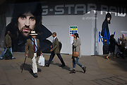 Pedestrians pass-by a large hoarding ad for an opening store of G-Star on London's Oxford Street. The to and fro of Londoners as they walk past the large image of the male model lends a sense of scale, of small people in reality to the oversized masculinity of a male model.