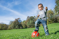 Portrait small boy stepping on red football meadow
