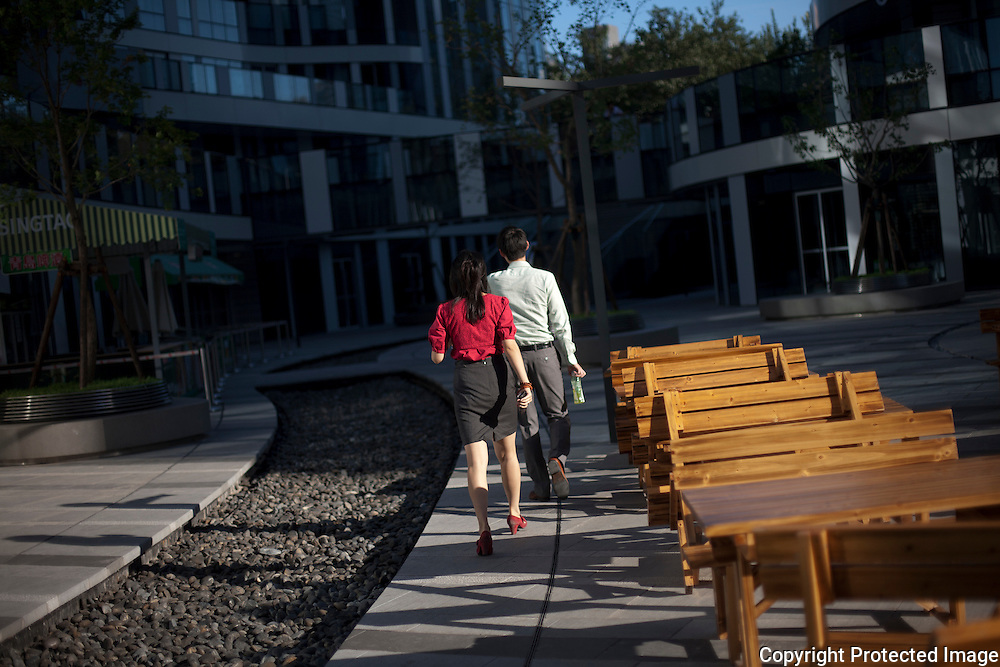 A Chinese man and woman walk through the new and still empty SOHO complex in Beijing. Construction of new commercial and residential complexes continue to sprout up in Beijing in spite an economy that is showing signs of cooling.