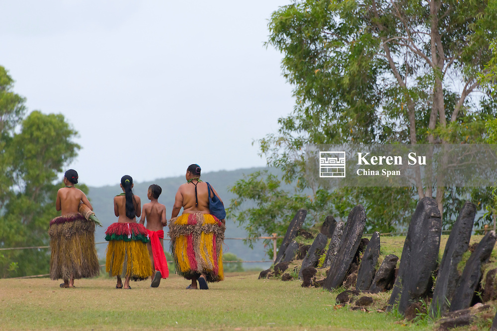 Yapese people in traditional clothing walk by stone money in the village, Yap Island, Federated States of Micronesia