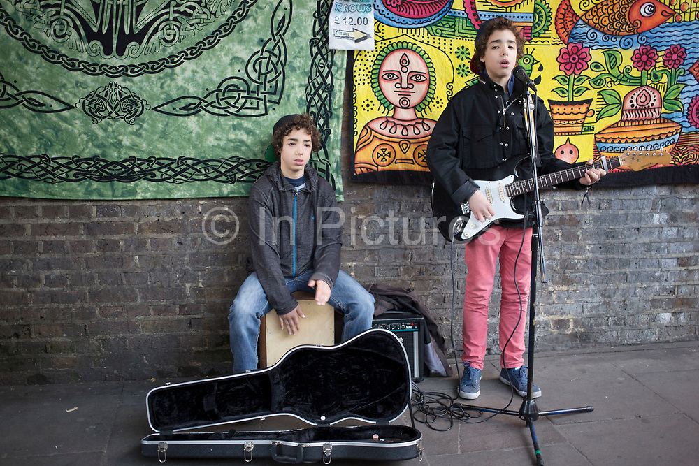 Twins busking in Camden Town, London, UK. With one of the boys on guitar and the other playing a box as a drum, these two boys impress with their rock based music.