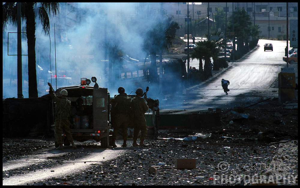 A Palestinian youth runs for cover as Israeli soldiers use tear gas during a clash in the West-bank city of Ramallah. (Photo © Jock Fistick)