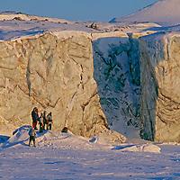 Polar tourists stand below a coastal glacier front at Inglefield Bay, Arctic Ocean.