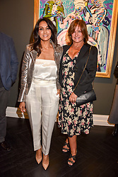 Left to right, Jackie St.Clair and Miranda Davis at a private view of work by Bradley Theodore entitled 'The Second Coming' at the Maddox Gallery, 9 Maddox Street, London England. 19 April 2017.