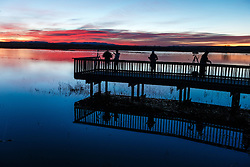 """Photographers and birders on  the """"Flight Deck"""" wildlife viewing dock at sunrise, waiting for birds, Bosque del Apache, National Wildlife Refuge, New Mexico, USA."""