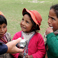 South America, Peru, Willoq. Kids of Willoq giggle at their image on a digital camera.