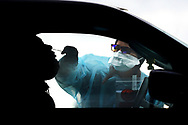 Workers from AMI Expeditionary Healthcare administer mid-nasal passage swab PCR tests to members of the public, as the Pennsylvania Department of Health opened a fee, 5-day drive-thru testing site at the William Penn Highway Park & Ride in Easton, Pennsylvania.