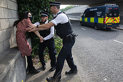 Metropolitan Police officers restrain a human rights activist trying to run into an access road in front of a large military vehicle during a protest against the DSEI 2021 arms fair at ExCeL London on 6th September 2021 in London, United Kingdom. The first day of week-long Stop The Arms Fair protests outside the venue for one of the world's largest arms fairs was hosted by activists calling for a ban on UK arms exports to Israel.