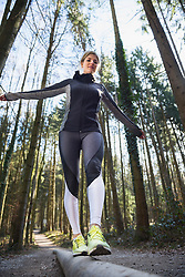 Young woman balancing on wooden log in forest