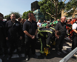 Members of the emergency services observe a minute's silence near to Grenfell Tower (background) in west London after a fire engulfed the 24-storey building on Wednesday morning.