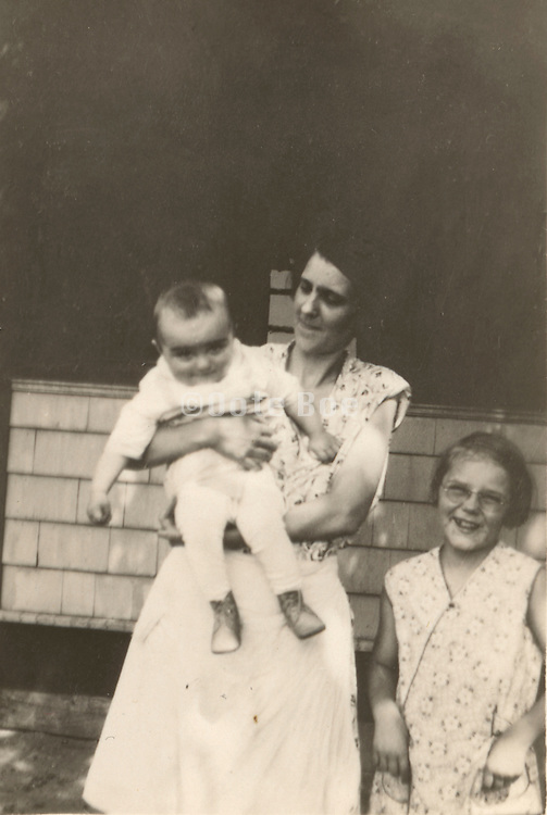 a mother posing with here two children