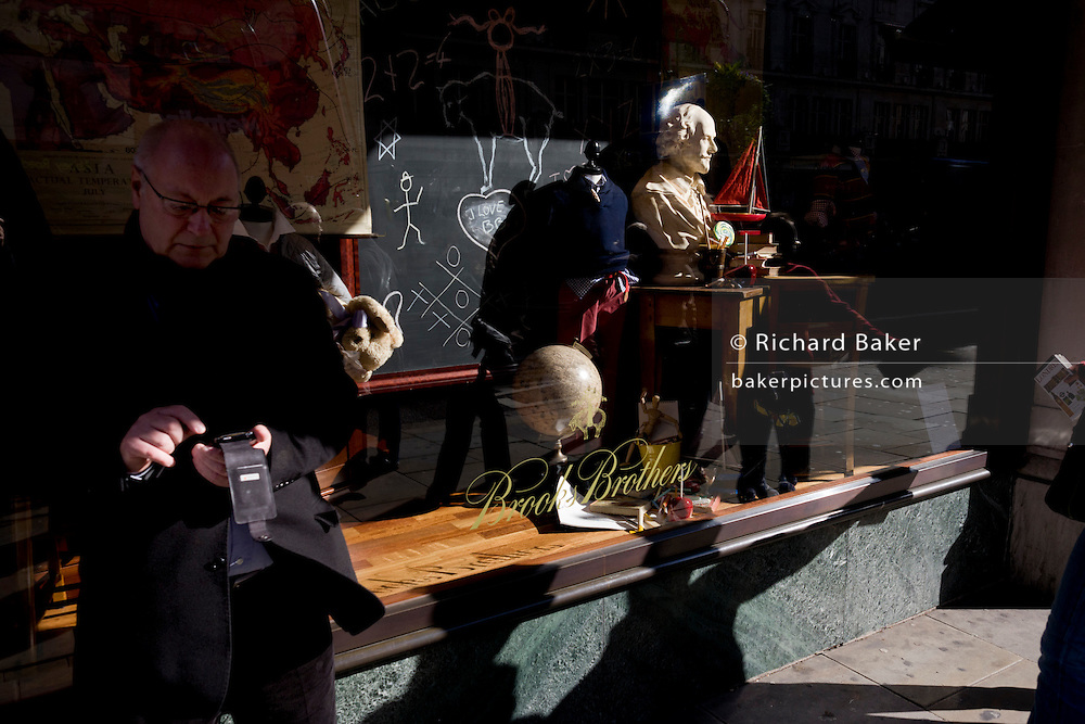 A man uses a smartphone near a head of English playright William Shakespeare whose bust is sunlit in a London shop window.