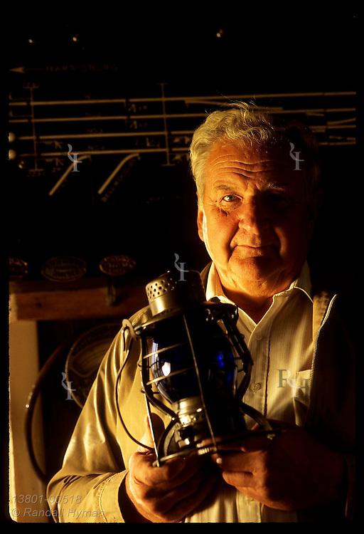 Charles Hazlett holds blue RR lantern once used to warn of derail device on tracks; Hollidaysburg. Pennsylvania