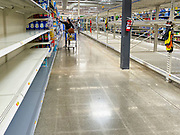 """15 MARCH 2020 - ANKENY, IOWA: A person shops in the empty toilet paper aisle at the Walmart store in Ankeny. Iowans started hoarding paper products and canned goods over the weekend as fears of coronavirus caused shortages spread. The Governor of Iowa announced Saturday night that the Coronavirus in Iowa had entered the """"community spread"""" phase when a person in Dallas County, in the Des Moines metropolitan area, tested positive for Coronavirus. As of Sunday morning, Iowa was reporting 18 people tested positive for Coronavirus.                     PHOTO BY JACK KURTZ"""
