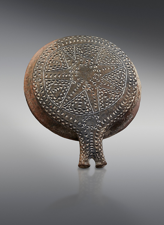 Cycladic terracotta 'frying pan' with incied star decoration from Chalandriani, Syros. Early Cycladic period II 2800-2300 BC), National Archaeological Museum Athens, Cat No 5153.  Grey background.<br /> <br /> <br /> These so called 'frying pans' wre created by the Keros-Syros culture and are their useage is uncertain. The compex geometric patterns on their bases suggest that they may have had some symbolic meaning and were used in religious of magical rituals. They could also have served practical purposes being used as dishes, mirror mounts, astrolabes or metris measured for salt traders. .<br /> <br /> If you prefer to buy from our ALAMY PHOTO LIBRARY  Collection visit : https://www.alamy.com/portfolio/paul-williams-funkystock/cycladic-art-artefacts.html Type into the LOWER SEARCH WITHIN GALLERY box to refine search by adding background colour, place, museum etc<br /> <br /> Visit our CYCLADIC CIVILISATIONS PHOTO COLLECTIONS for more photos to download or buy as wall art prints https://funkystock.photoshelter.com/gallery-collection/Cycladic-civilisation-Ancient-Greek-Artefacts-art-Photos-Pictures-Images/C0000CmevVvnC.XU