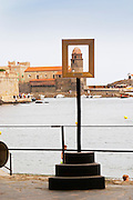 A frame symbolising Collioure as a village historically visited by many painters, such as can be found in many places in the village, on locations from where famous paintings have been painted. The church Eglise Notre Dame des Anges, our lady of the angels. With its emblematic church tower. Collioure. Roussillon. France. Europe.
