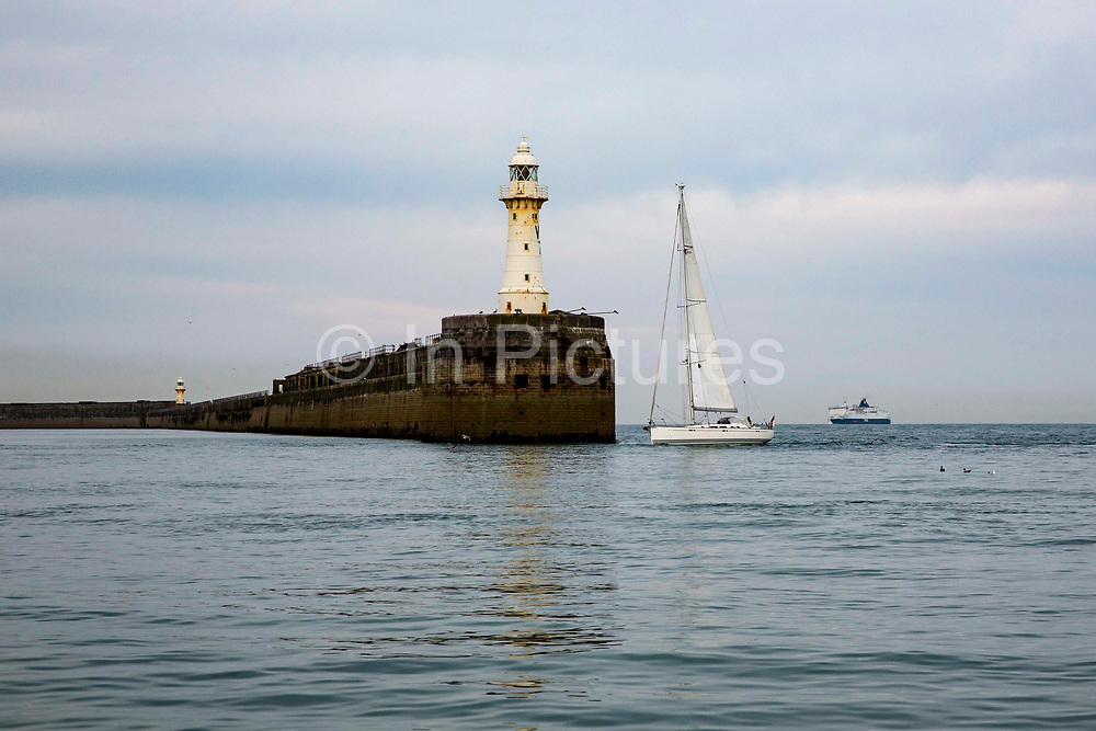 A white sail boat sails past Dover Breakwater Lighthouse, leaving Dover harbour in the early morning, Kent, England, United Kingdom. A large ferry boat is also returning to the port.