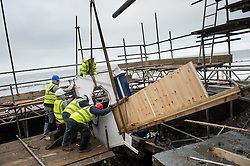 © London News Pictures. Aberystwyth, UK. 22/01/2014.<br /> Workmen remove the last sections of the iconic 1920'€™s public shelter that was destroyed by the huge storms at Aberystwyth in early January 2014. The waves gouged out the hollow foundations underneath the Grade 2 listed building causing its collapse. The remains have now ben taken away for replacement and repair. Photo credit: Keith Morris/LNP<br /> <br /> <br /> photo ©keith morris