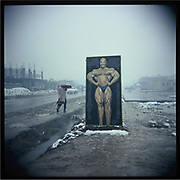 A woman walks past a sign board promoting a gym in the outskirts of Kabul.