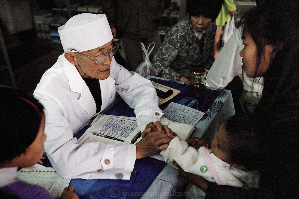 A traditional medicine doctor surrounded by his patients in the Fu Lin Tang Pharmacy in Kunming, China. The doctors, and all those in the line, listen to a series of health ailments, after which the doctor prescribes specific prescriptions of herbs and insects. From the project, Man Eating Bugs: The Art and Science of Eating Bugs.