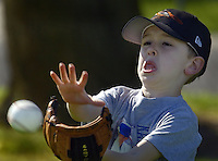 Young baseball player, Jonathan Hicks, 6, learns to catch the ball during practice at Ellen Feickert Elementary School in Elk Grove, Saturday March 13, 2004. With the growth of the Elk Grove comes other demands like the large number of children signing up to play in a baseball league.