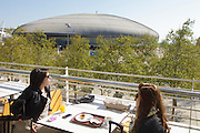 Two ladies on a terrace with Atlantic Pavillion at Nations Park was built for the Expo98 world exhibition in Lisbon. The Park became the most modern part of town with landmark buildings from world-recognized architects.