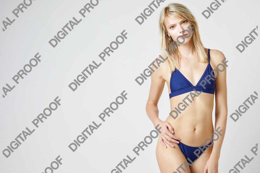 Girl in bikini isolated in studio with a white background and with a frontal view