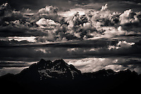 monochrome of clouds in unsettled air over The Brothers, a mountain of the Olympic Range seen from Puget Sound after sunset