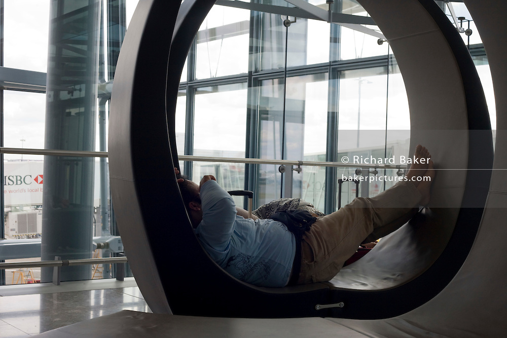 "A resting passenger sleeps on a specially-designed circular couch near airport gates during his layover transit period at Heathrow airport's Terminal 5. The man has jet lag after a long-haul flight across continents and now needs to re-adjust to British Summer time (BST). Vast sheets of window glass lets in natural daylight in this tranquil area where travellers can remain largely undisturbed from the otherwise hectic airport terminal created by the Richard Rogers Partnership (now Rogers Stirk Harbour and Partners). From writer Alain de Botton's book project ""A Week at the Airport: A Heathrow Diary"" (2009)."